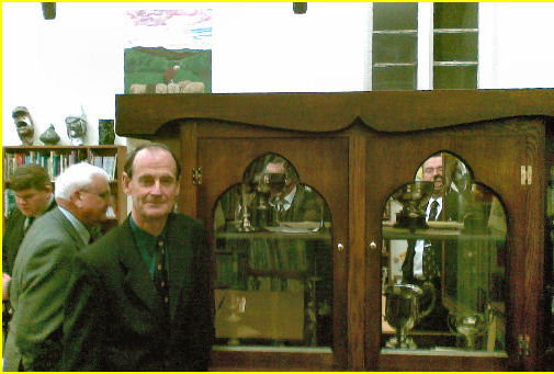 Former Maths teacher Des Williams in front of the John Arbery Memorial Cabinet in the Resource Centre